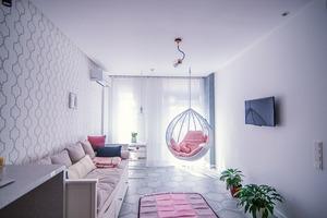 Світла квартира з квітковим декором та кріслом-гойдалкою